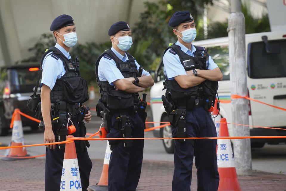 """Police officers stand guard outside local court in Hong Kong Thursday, July 22, 2021. Hong Kong police charged two top editors and two editorial writers at Apple Daily with collusion weeks after the city's largest pro-democracy newspaper was forced to cease publication and its assets were frozen. All four were charged with conspiring to """"collude with a foreign country or with external elements to endanger national security"""" under the city's year-old national security law and appeared in court Thursday. (AP Photo/Vincent Yu)"""