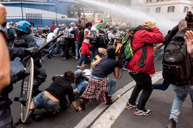 ROME, ITALY - OCTOBER 09: Police in riot gear clash with protesters during a protest against the