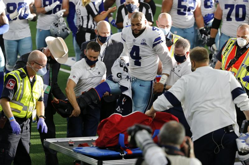 Dallas Cowboys quarterback Dak Prescott (4) is assisted onto a cart after suffering a leg injury. (AP Photo/Michael Ainsworth)