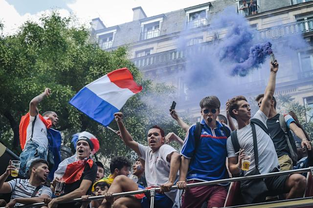 <p>People hold French national flags as they stand on a bus prior to the start of the Russia 2018 World Cup final football match between France and Croatia, in Paris on July 15, 2018. (Getty Images) </p>