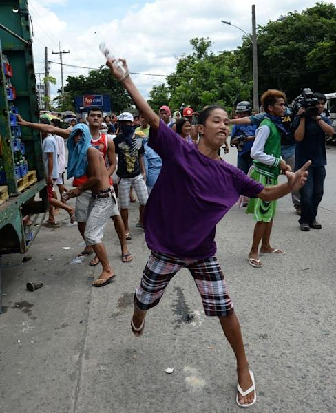 Philippine slum dwellers throw botltles at anti-riot policemen (not pictured) during clashes in Manila, on July 1, 2013. Slum dwellers hurled rocks, improvised explosives and human excrement fought running battles with riot police around a sprawling Manila shanty town that is set for redevelopment