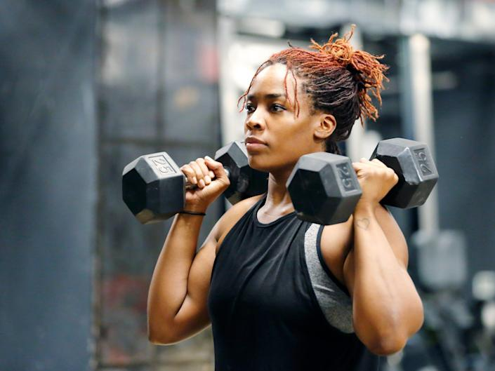 A woman lifting two dumbbells at her shoulders.