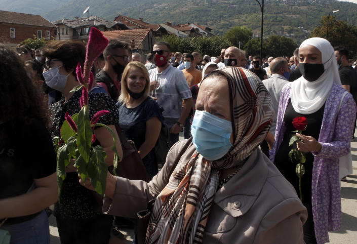 Women carry flowers to honor the victims in the burned out makeshift hospital in North Macedonia's northwestern town of Tetovo, Saturday, Sept. 11, 2021. Hundreds of people have marched Saturday in northwestern town of Tetovo to honor their 14 countrymen killed in a deadly fire that broke earlier this week and destroyed COVID-19 field hospital. (AP Photo/Boris Grdanoski)