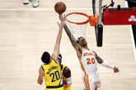 Atlanta Hawks forward John Collins (20) lays in a shot as Indiana Pacers forward Doug McDermott (20) defends during the fourth quarter of an NBA basketball game Saturday, Feb. 13, 2021, in Atlanta. (AP Photo/Butch Dill)