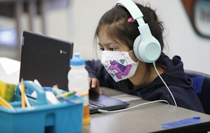 """WEST HOLLYWOOD, CA - MARCH 18: Second grade student Sophia Rivera, 8, completing online study while sitting in front of the BARD HVAC unit with latest in HVAC technology in the """"Beyond The Bell"""" classroom for students of employees on campus at West Hollywood Elementary School as Los Angeles Unified School District (LAUSD) Board Member Nick Melvoin, representing District 4 visits West Hollywood Elementary School and various other schools in his district to do an official check on preparations for reopening. The walking tour included the principal, Dr. Elizabeth Lehmann, LAUSD officials, a parent, West Hollywood Mayor Lindsay Horvath and Franny Parrish, with (CSEA), which represents school clerical workers and library aides, as they viewed modifications made to the school with COVID-19 considerations. West Hollywood Elementary School on Thursday, March 18, 2021 in West Hollywood, CA. (Al Seib / Los Angeles Times)."""