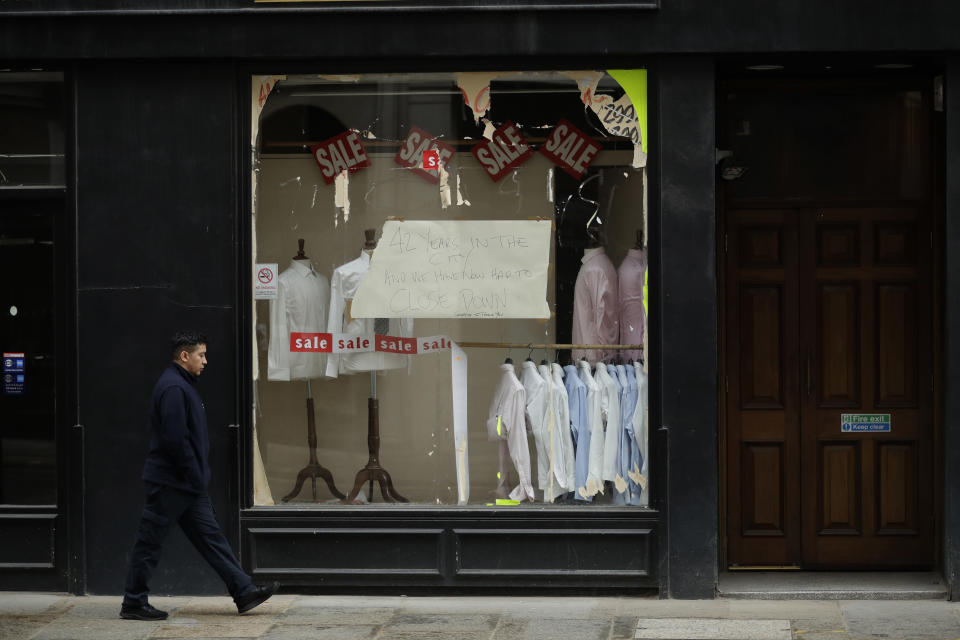 """A sign in the window of the """"Suited & Booted"""" gentlemen's outfitters and tailors states that they have had to close down after 42 years in the City, which has happened since the start of the coronavirus outbreak, in the City of London financial district of London, during England's third coronavirus lockdown, Thursday, March 25, 2021. The pandemic has battered the British economy, which suffered its deepest recession in more than 300 years. Pubs, restaurants, theaters, hair salons and all stores selling nonessential items such as books and footwear have spent much of the past year closed. (AP Photo/Matt Dunham)"""