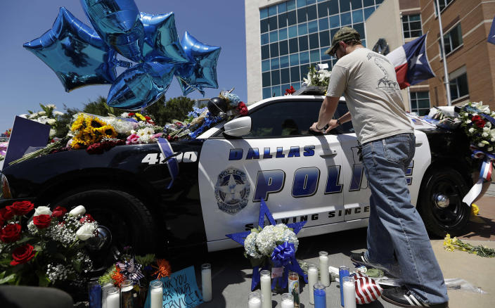 <p>Michael O'Mahoney, a former police officer, places his patch on a make-shift memorial at the Dallas police headquarters, Friday, July 8, 2016, in Dallas. Five police officers are dead and several injured following a shooting in downtown Dallas Thursday night. (AP Photo/Eric Gay) </p>