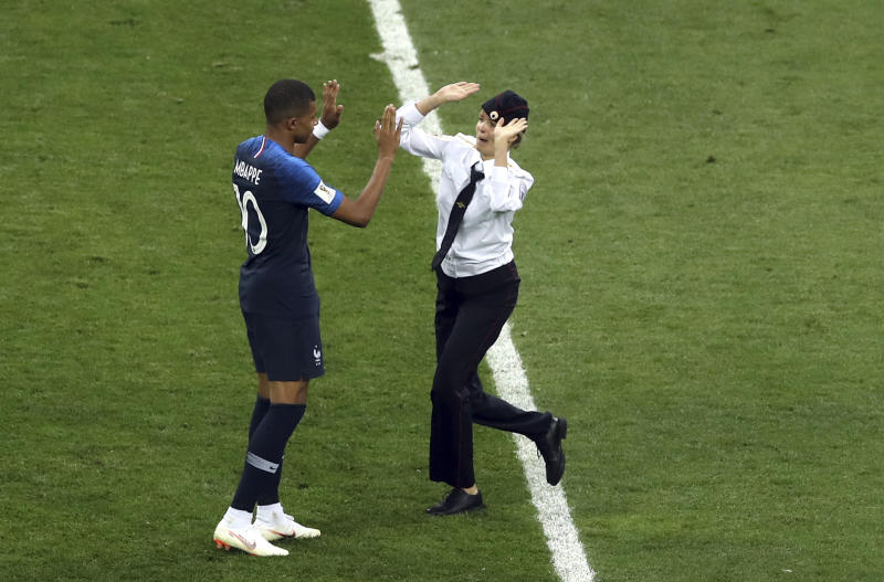 A woman who invaded the pitch approaches France's Kylian Mbappe during the final match between France and Croatia at the 2018 soccer World Cup in the Luzhniki Stadium in Moscow, Russia, Sunday, July 15, 2018. (AP Photo/Thanassis Stavrakis)