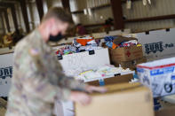 A soldier sifts through donations at Fort Bliss' Doña Ana Village, in New Mexico, where Afghan refugees are being housed, Friday, Sept. 10, 2021. The Biden administration provided the first public look inside the U.S. military base where Afghans airlifted out of Afghanistan are screened, amid questions about how the government is caring for the refugees and vetting them. (AP Photo/David Goldman)