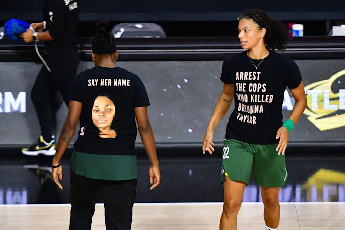 """Two basketball players wear black t-shirts that read, respectively, """"Say her Name"""" above a picture of Breonna Taylor, and """"Arrest the cops who killed Breonna Taylor."""""""