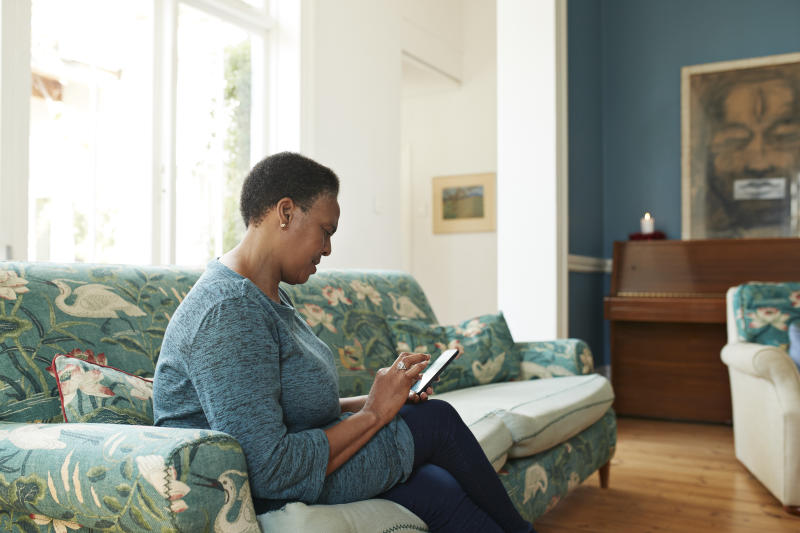 Side view of senior woman using smart phone while relaxing on sofa at home