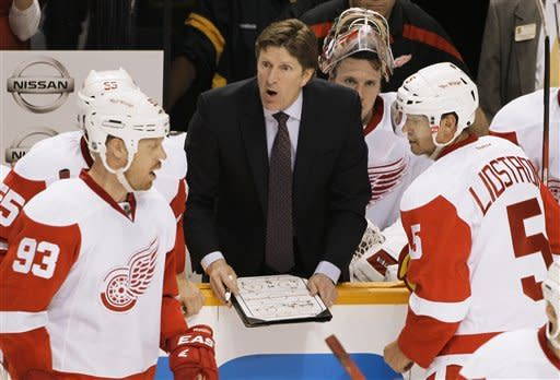 Detroit Red Wings head coach Mike Babcock, center, talks with players, including Johan Franzen (93), of Sweden, and Nicklas Lidstrom (5), also of Sweden, in the third period against the Nashville Predators in Game 1 of a first-round NHL hockey playoff series on Wednesday, April 11, 2012, in Nashville, Tenn. The Predators won 3-2. (AP Photo/Mark Humphrey)