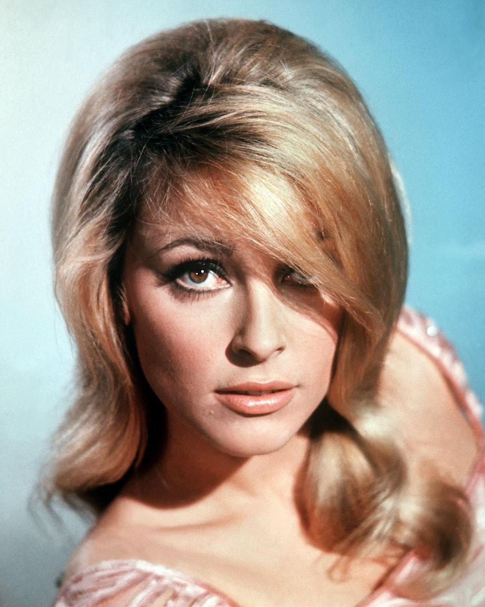 <p>The actress was also known for her signature look of bold false eyelashes and blonde bangs—a look that soon became the aesthetic of the era. </p>
