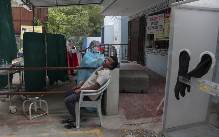 A health worker takes a nasal swab sample to test for COVID-19 in Hyderabad, India, Tuesday, Sept. 29, 2020. India confirmed coronavirus tally has reached 6 million cases, keeping the country second to the United States in number of reported cases since the pandemic began. (AP Photo/Mahesh Kumar A.)