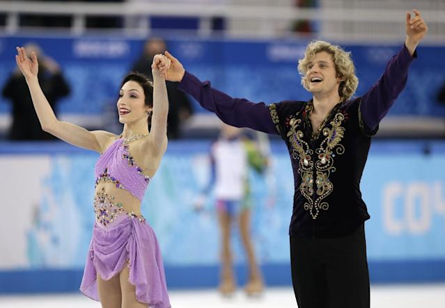 Meryl Davis and Charlie White of the United States acknowledge the crowd after completing their routine in the ice dance free dance figure skating finals at the Iceberg Skating Palace during the 2014 Winter Olympics, Monday, Feb. 17, 2014, in Sochi, Russia. (AP Photo/Darron Cummings)