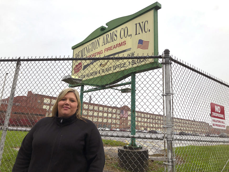 Jacquie Sweeney stands outside the Remington firearms factory in Ilion, N.Y., Tuesday, Oct. 20, 2020. Jacquie Sweeney and her husband were among almost 600 workers fired by the company this week, a few months after Remington Outdoor Co. sought bankruptcy protection for the second time in two years. Successful bidders for the idled plant in bankruptcy proceedings have said they plan to restart at least some production, though details remain scarce.. (AP Photo/Michael Hill)