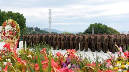 North Korean soldiers salute near floral tributes in North Korea