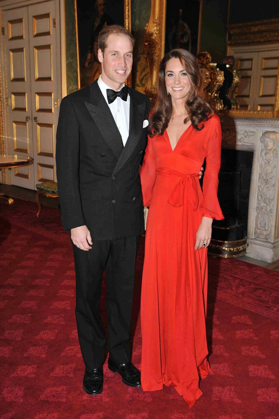<p>Kate wore a vibrant red wrap dress by Beulah London for a fundraising gala, accessorising with a gold Wilbur and Gussie clutch.</p><p><i>[Photo: PA]</i></p>