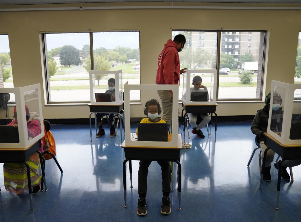 FILE - In this Sept. 8, 2020, file photo, paraprofessional Jaevon Walton, center, reminds a student to wear his face mask in a learning pod of second through seventh graders at Harvest Best Academy in Minneapolis. (David Joles/Star Tribune via AP, File)