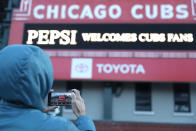 A person takes a photo of the Wrigley Field marquee, early morning on the opening day baseball game between the Chicago Cubs and the Pittsburgh Pirates, Thursday, April 1, 2021 at Chicago. From New York to Seattle and everywhere in between, it's a much different opening day in 2021. Fans are back at the ballpark after they were shut out during the regular season last year because of the coronavirus pandemic. (AP Photo/Shafkat Anowar)