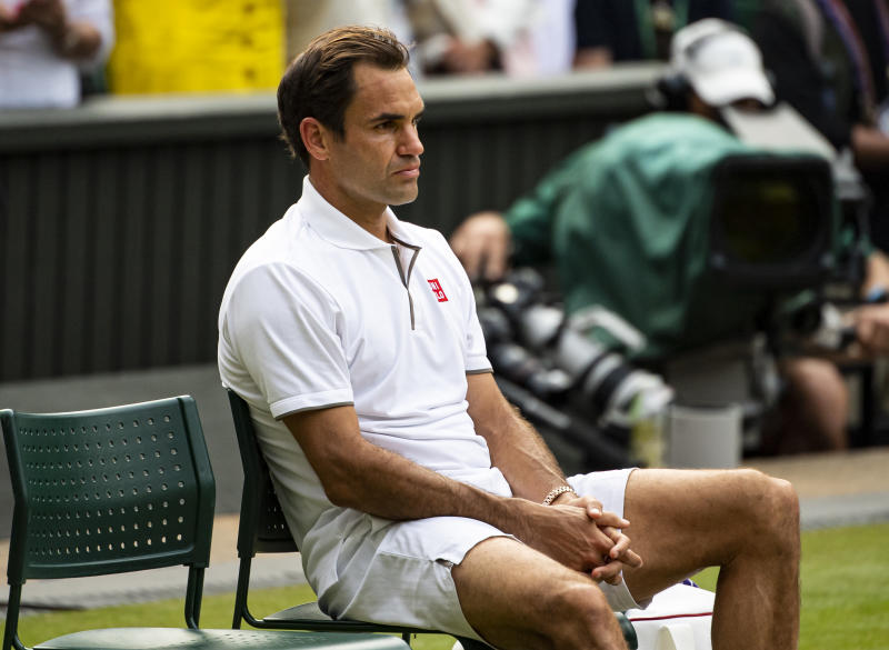 Roger Federer looks dejected and sits down after losing against Novak Djokovic.