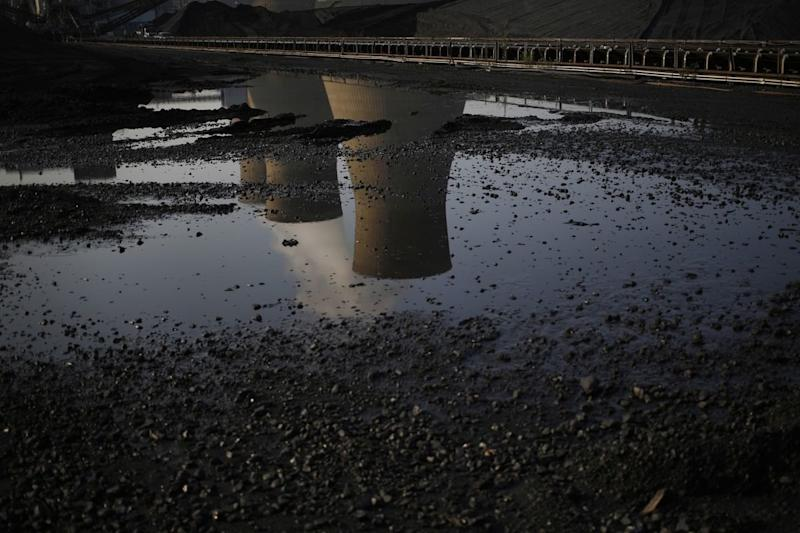 Cooling towers are reflected in a puddle at the American Electric Power Company's coal-fired John E. Amos Power Plant in Winfield, West Virginia. (Bloomberg)