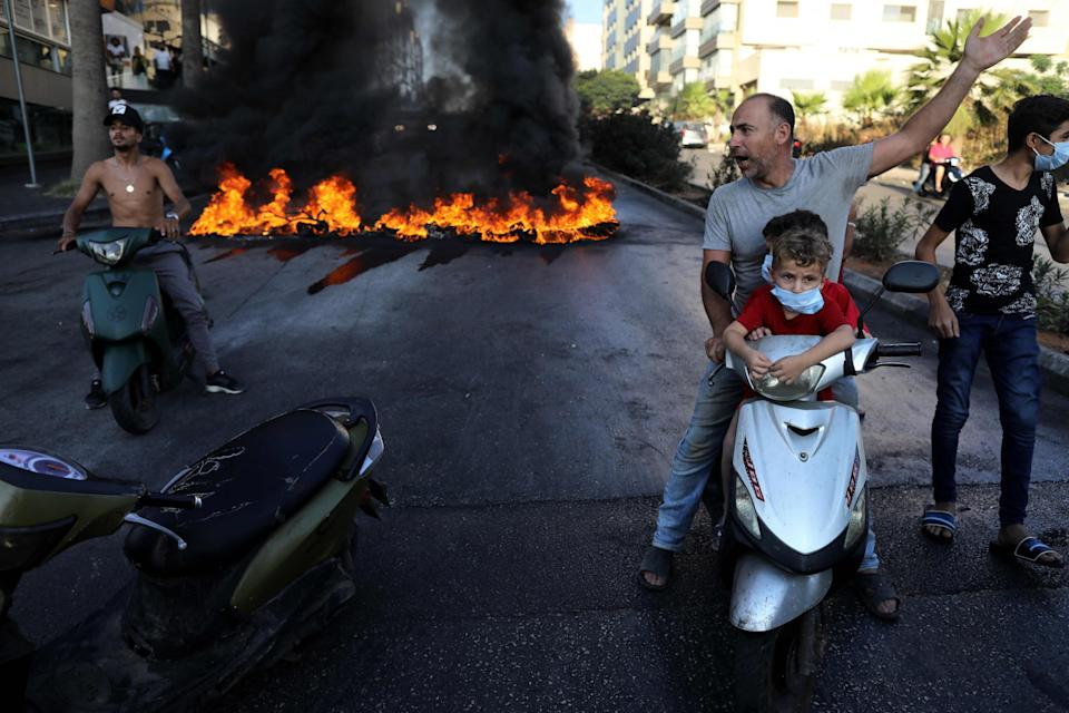 A Lebanese man on a scooter with two children gestures near tires set on fire during a protest at a main road in Lebanon's capital Beirut against dire conditions amidst the ongoing economical and political crisis (AFP via Getty Images)