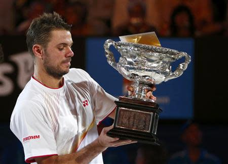 Stanislas Wawrinka of Switzerland poses with Norman Brookes Challenge Cup after defeating Rafael Nadal of Spain in their men's singles final match at the Australian Open 2014 tennis tournament in Melbourne