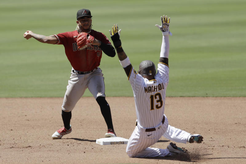 Arizona Diamondbacks second baseman Ketel Marte throws to first to complete the double play as San Diego Padres' Manny Machado (13) slides into second after being forced during the fourth inning of a baseball game Monday, July 27, 2020, in San Diego. Tommy Pham was out at first. (AP Photo/Gregory Bull)