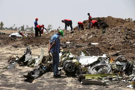 A man watches debris at the scene of the Ethiopian Airlines Flight ET 302 plane crash, near the town of Bishoftu, southeast of Addis Ababa