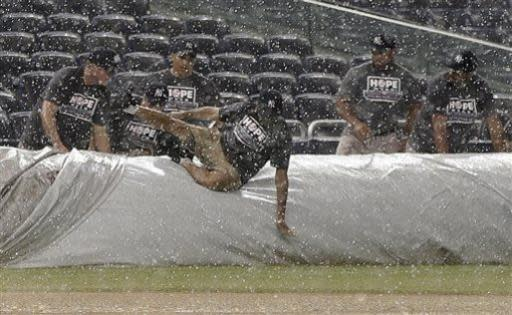 A groundskeeper slips and falls as others roll the tarp onto the field during a rain delay in the New York Yankees baseball game against the Kansas City Royals, Monday, July 8, 2013, in New York. (AP Photo/Kathy Willens)