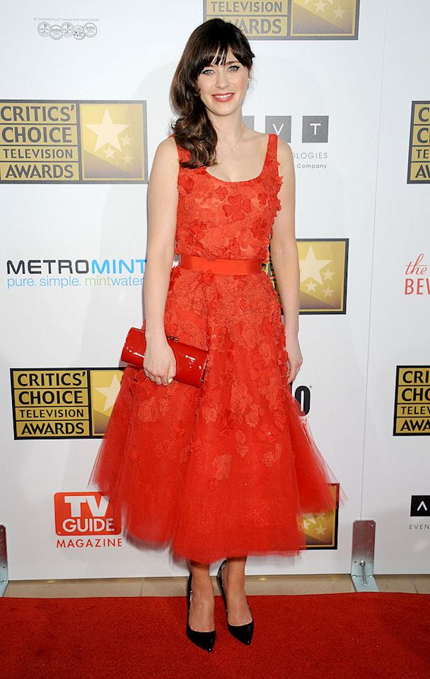 "Also in attendance ... ""New Girl"" cutie and Best Actress in a Comedy Series winner Zooey Deschanel, who, like Regina, opted for a red frock. This one, however, was designed by Oscar de la Renta and featured a delicate floral applique. A patent leather clutch and black Louboutin pumps made for the perfect accessories. (6/18/2012)"
