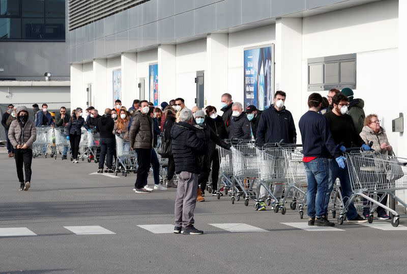 People queue at a supermarket outside the town of Casalpusterlengo