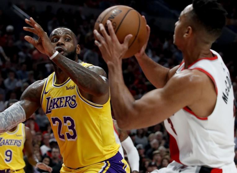 LeBron James defends against Trail Blazers guard CJ McCollum in the first quarter.