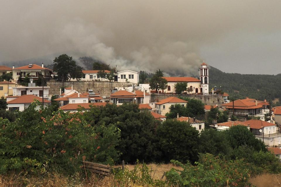 Flames burn a forest during a wildfire in Kourkouloi village on the island of Evia, about 150 kilometers (93 miles) north of Athens, Greece, Thursday, Aug. 5, 2021. Forest fires fueled by a protracted heat wave raged overnight and into Thursday in Greece, threatening the archaeological site at the birthplace of the modern Olympics and forcing the evacuation of dozens of villages. (AP Photo/Thodoris Nikolaou)