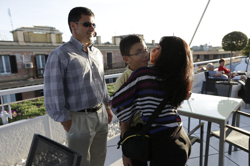 Jake Finkbonner, of Ferndale, Washington, center, is hugged by his mother Elsa, as his father Donny looks at them, after an interview with the Associated Press, in Rome, Thursday, Oct. 18, 2012. Jake was infected with a flesh-eating bacteria in 2006, when he was five years old, and his prognosis was so grave that his parents had last rites performed and were discussing donating his organs. The Vatican determined that Jake's cure was a miracle due to the intercession of Kateri Tekakwitha, a 17th century Native American who is among seven people who will be declared saints on Sunday by Pope Benedict XVI. (AP Photo/Alessandra Tarantino)
