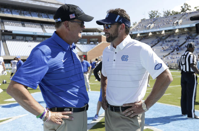 FILE - In this Sept. 23, 2017, file photo, Duke coach David Cutcliffe, left, and North Carolina coach Larry Fedora speak prior to an NCAA college football game in Chapel Hill, N.C. Fedora's Tar Heels have lost 19 of 24 games dating to November 2016 entering Saturday's trip to Duke. (AP Photo/Gerry Broome, File)