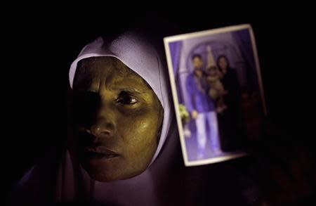 A Muslim woman holds up an image of her family members who disappeared during the civil war with the Liberation Tigers of Tamil Eelam (LTTE) at a vigil to commemorate the international day of the disappeared in Colombo August 30, 2013. REUTERS/Dinuka Liyanawatte