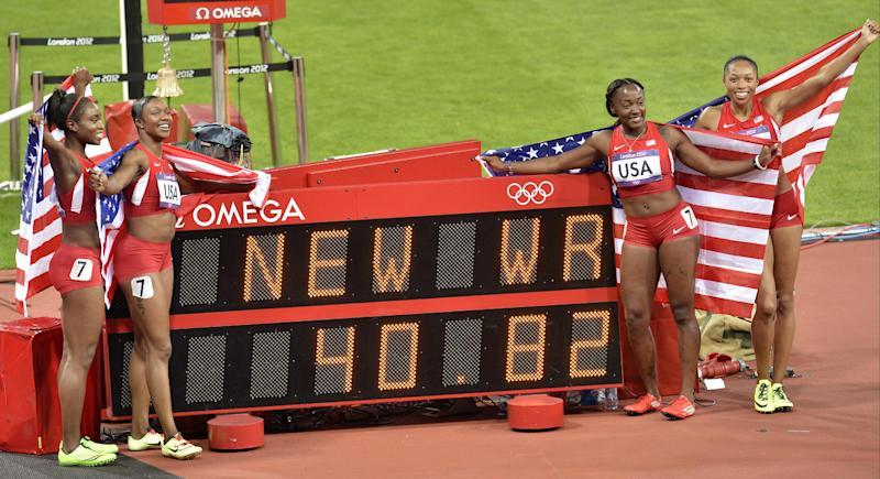 United States' women's relay team from left, Tianna Madison, Carmelita Jeter, Bianca Knight, and Allyson Felix pose for a photo by the clock showing their world record time, during the athletics in the Olympic Stadium at the 2012 Summer Olympics, London, Friday, Aug. 10, 2012. (AP Photo/Martin Meissner)
