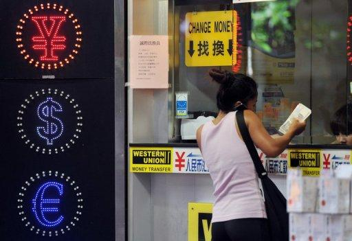 A woman exchanges money at a currency exchange shop in Hong Kong on September 15, 2011