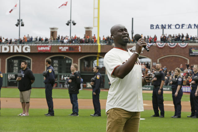 "Isaiah Johnson, with the musical ""Hamilton,"" sings the national anthem as first responders of California wildfires stand in the background before the start of an opening day baseball game between the San Francisco Giants and the Tampa Bay Rays, Friday, April 5, 2019, in San Francisco. (AP Photo/Eric Risberg)"