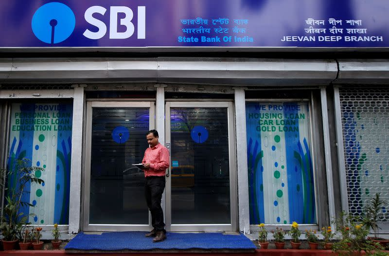 A man checks his mobile phones in front of State Bank of India (SBI) branch in Kolkata