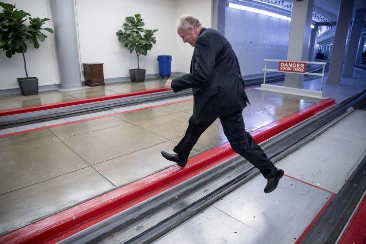 Sen. Jerry Moran, R-Kan., jumps over the Senate subway tracks to evade reporters as he arrives on Capitol Hill in Washington on Tuesday. Moran's leap follows the collapse of the health care bill, in which he played a key role. (Photo: Andrew Harnik/AP)
