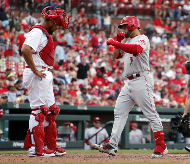 Cincinnati Reds' Eugenio Suarez, right, scores past St. Louis Cardinals catcher Francisco Pena after hitting a two-run home run during the 10th inning of a baseball game Sunday, Sept. 2, 2018, in St. Louis. (AP Photo/Jeff Roberson)