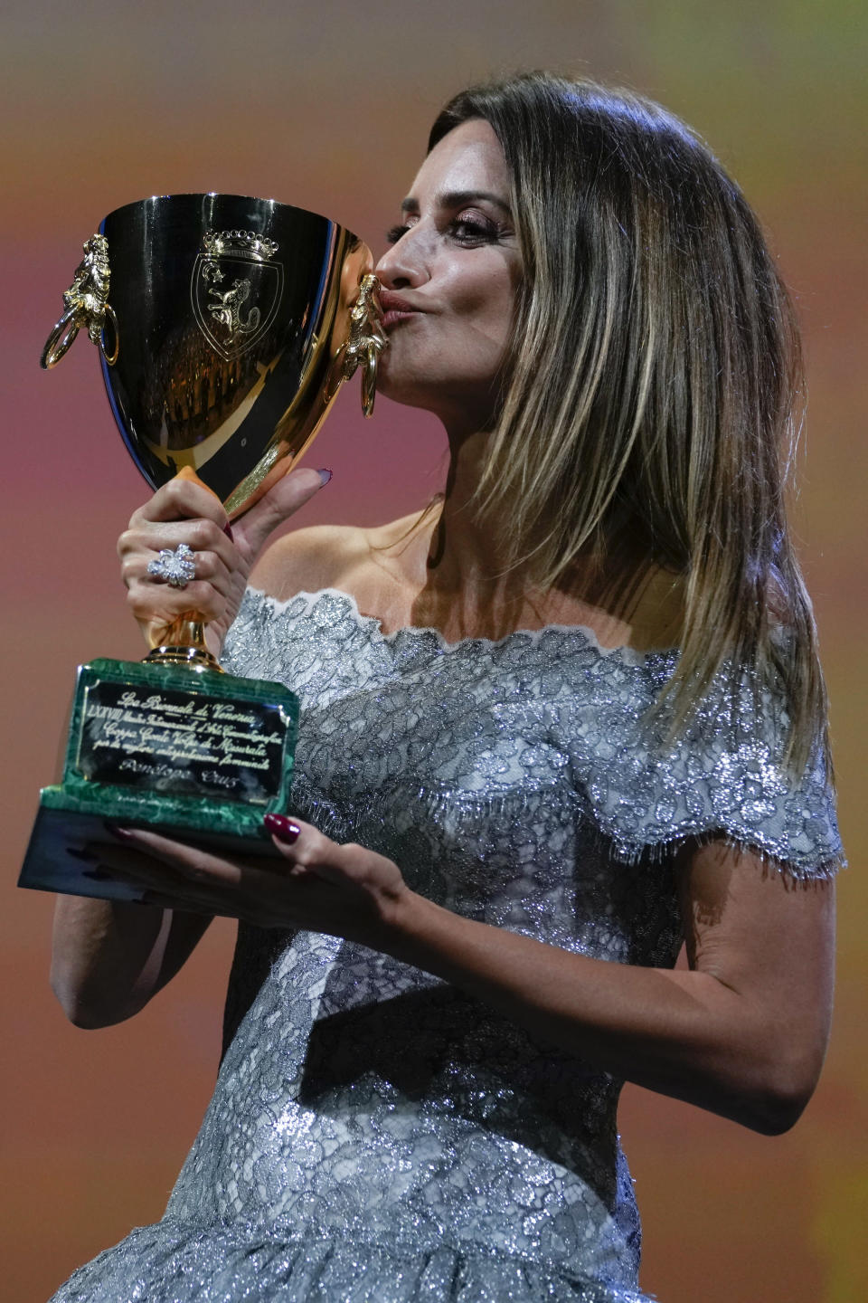 Penelope Cruz kisses the Coppa Volpi Best Actress award for 'Parallel Mothers' onstage at the closing ceremony during the 78th edition of the Venice Film Festival in Venice, Italy, Saturday, Sept. 11, 2021. (AP Photo/Domenico Stinellis)