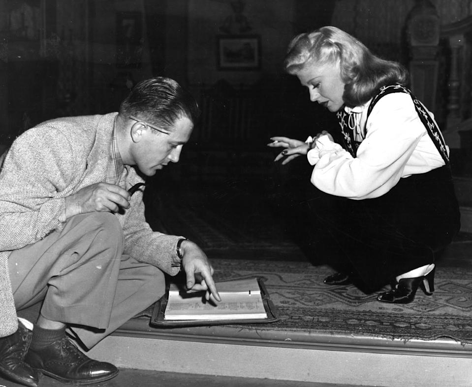Actress and dancer Ginger Rogers (1911 -1995 ) discusses her new role in 'Tender Comrade' with her director Edward Dmytryk.     (Photo by Hulton Archive/Getty Images)