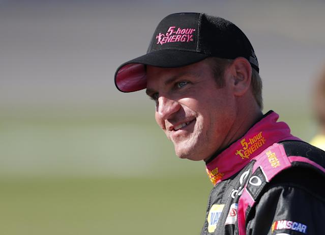 FILE - In this Oct. 4, 2013 file photo, Clint Bowyer smiles during qualifying for a NASCAR Sprint Cup series auto race at Kansas Speedway in Kansas City, Kan. Bowyer is heading home to Kansas Speedway this weekend with a new wife, a baby on the way and now a three-year contract extension that will keep him with Michael Waltrip Racing. The team announced the deal Monday, May 5, 2014, a day after Bowyer drove his No. 15 Toyota to a third-place finish at Talladega. (AP Photo/Orlin Wagner, File)