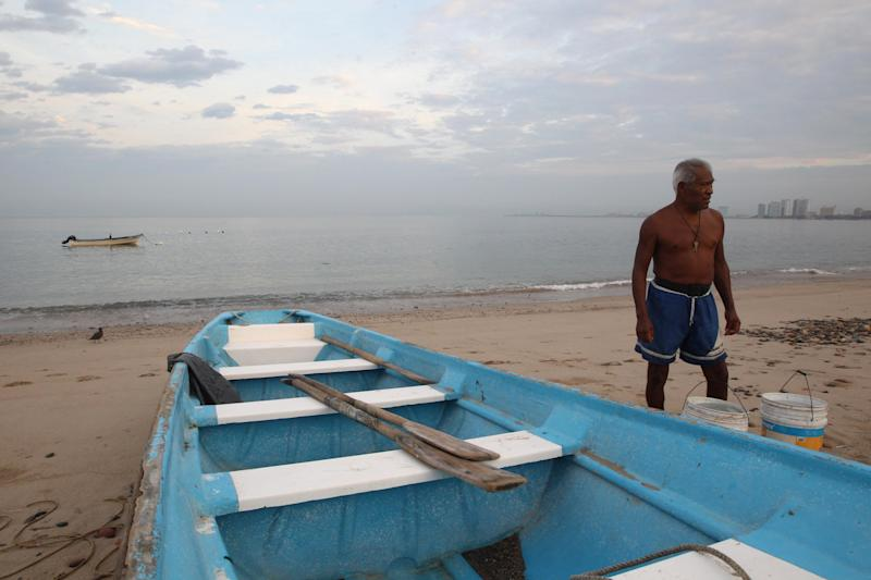 A fisherman walks next to his boat in the resort city of Puerto Vallarta, Mexico, Friday, May 25, 2012. Hurricane Bud lost a little of its sting early Friday, but remained a potent Category 2 storm as it headed toward a string of laid-back beach resorts and small mountain villages on Mexico's Pacific coast south of Puerto Vallarta. (AP Photo / Bruno González)