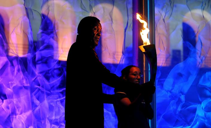 Rafer Johnson holds the torch after lighting the cauldron during the opening ceremony for the World Games at the Coliseum.