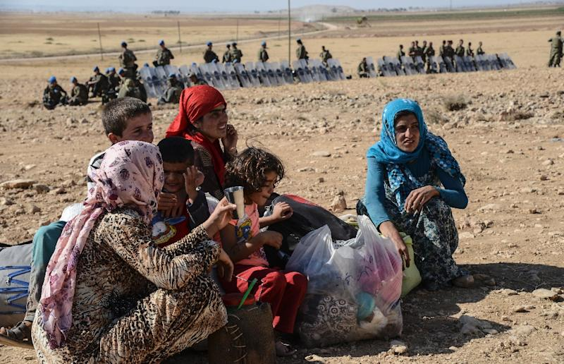 Syrian Kurds gather after crossing into Turkey near the southeastern town of Suruc in Sanliurfa province, on September 19, 2014